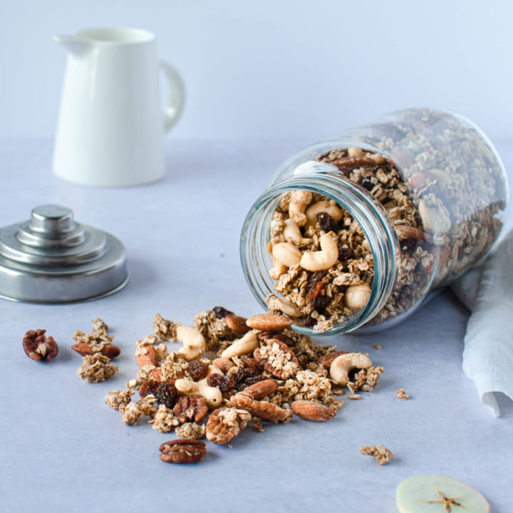 A glass jar on it's side and granola falling out on the table from the jar.