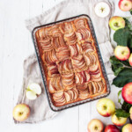 Sugar-free and gluten-free apple tart in glass pan with fresh apple around it.