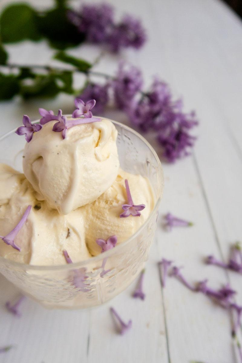 Vanilla ice cream garnished with lilac flowers in a glass bowl