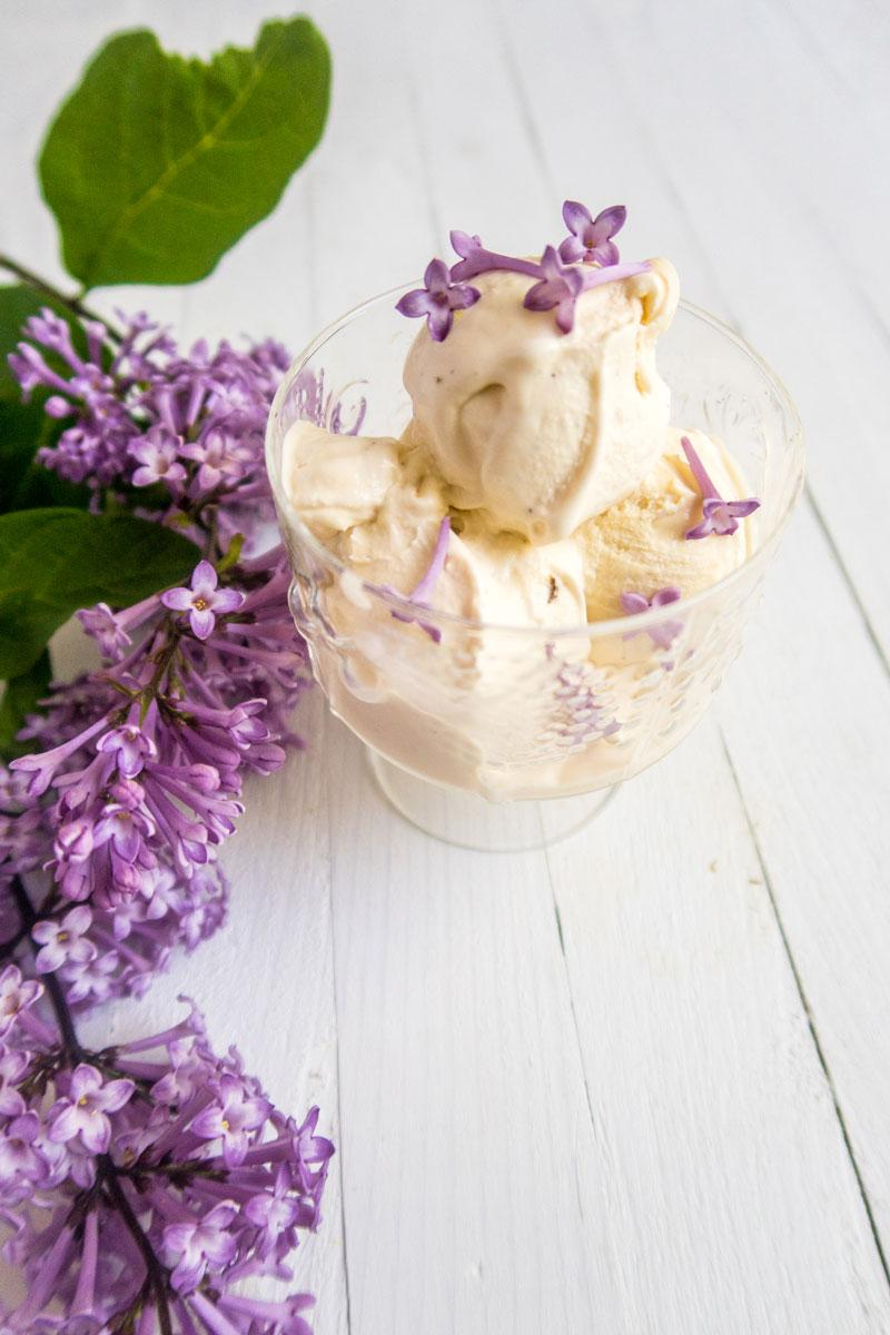 Three balls of vanilla ice cream garnished with lilac flowers in a vintage class bowl