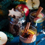 Kaksi glögimukillista omenaglögiä. Glögit on koristeltu omenasiivuilla appelsiinilohkoilla, kanelitangoilla ja tähtianiksilla. Glögin kanssa on tarjolla pipareita lasipurkissa.