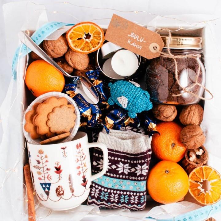 Lahjalaatikko, jossa on purkillinen joulukahvia, muki, villasukat, konvehteja, tuikkuja, pähkinöitä ja joulukuusenkoriste.