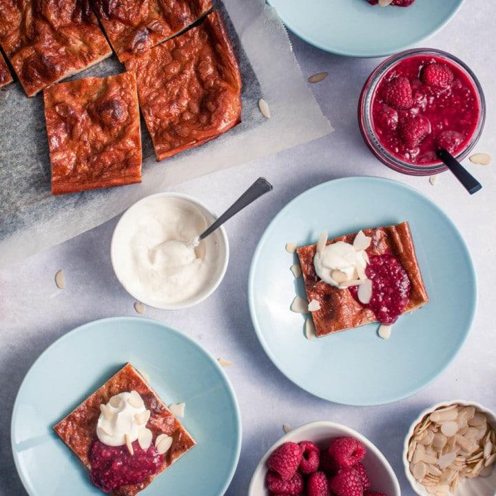 Gluteenitonta pannukakkua pellillä ja pannukakkupaloja lautasille. Pannukakkupalojen päälle on annosteltu vadelmahilloa ja kermavaahtoa.