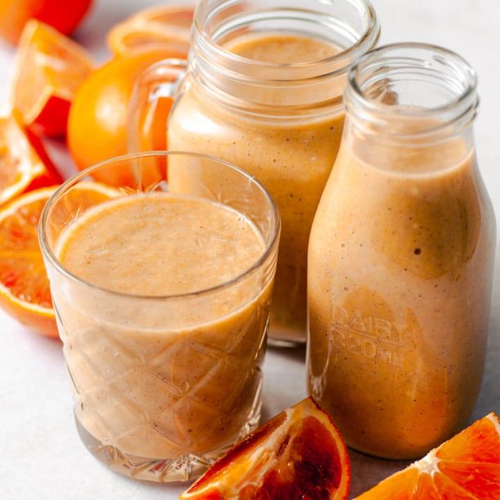 Kolme lasia appelsiinismoothieta ja koristeena veriappelsiininlohkoja