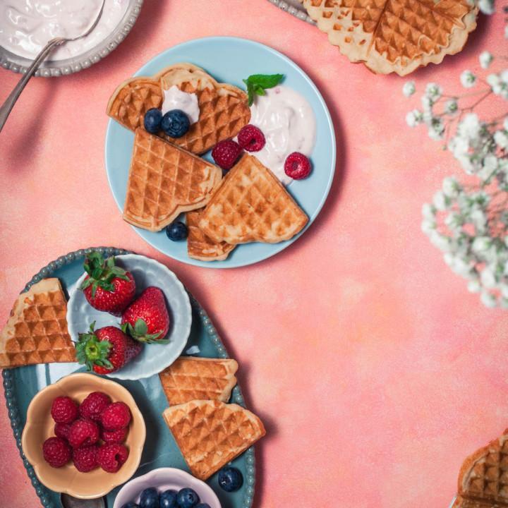 Oranssilla taustalla sydämiksi leikattuja sitruunavohveleita sinisellä lautasella. Kolme kulhoa marjoja, kulhot ovat lautasen päällä. Harsokukkia ja vadelmarahkaa.