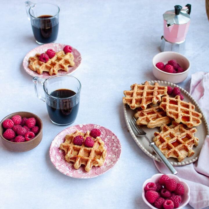 Kauravohveilta lautasilla ja tarjoiluvadilla sekä kaksi kuppia kahvia.