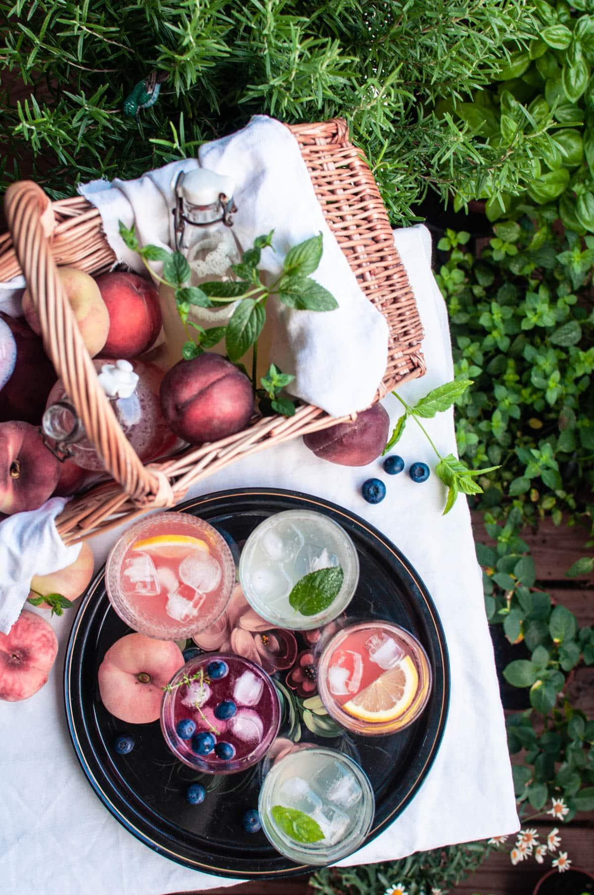 Ylhäältä otettu kuva. Pöydällä on kori, jossa on limonadipulloja ja persikoita sekä tarjotin, jolla on viisi lasillista limonadia.