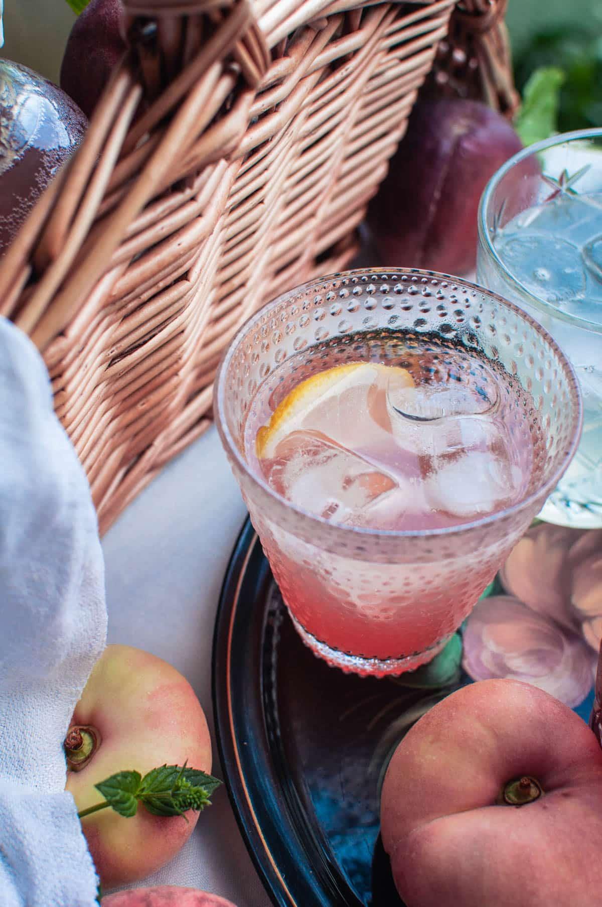 Lähikuva persikkalimonadista lasissa. Koristeena puolikas sitruunaviipale. Lasin ympärillä on littupersikoita.