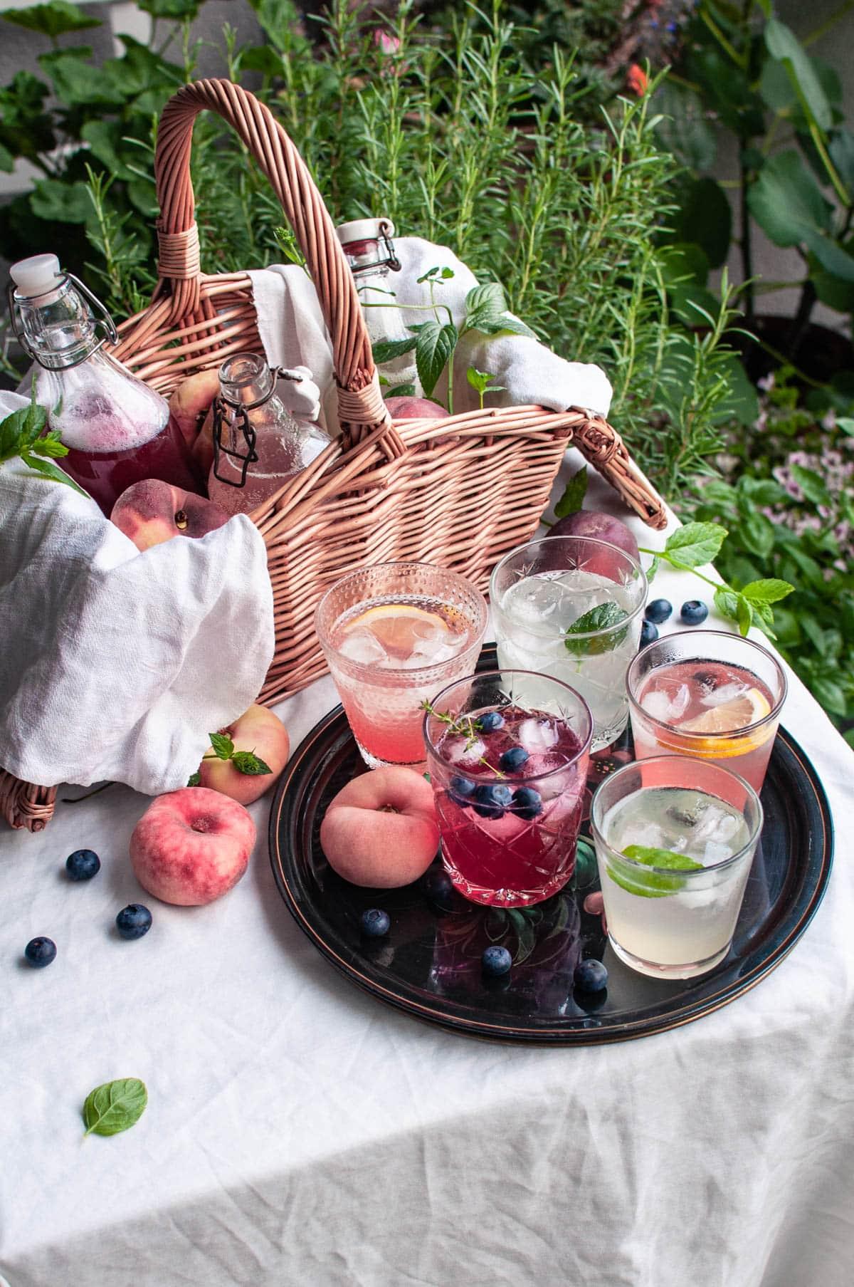 Pöydällä kori, jossa on limsapulloja ja persikoita sekä tarjotin, jolla on viisi lasillista limonadia