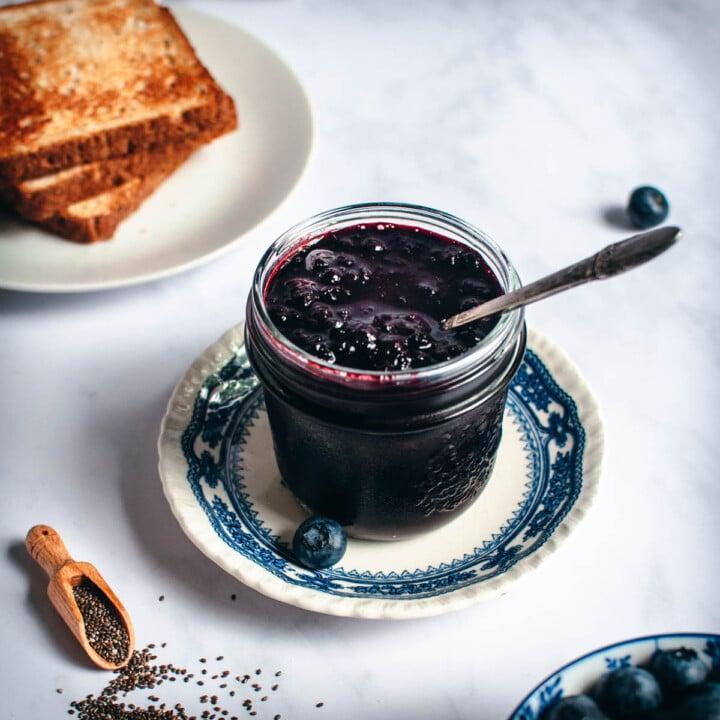 Sokeriton mustikkahillo lasitölkissä sinisellä lautasella.