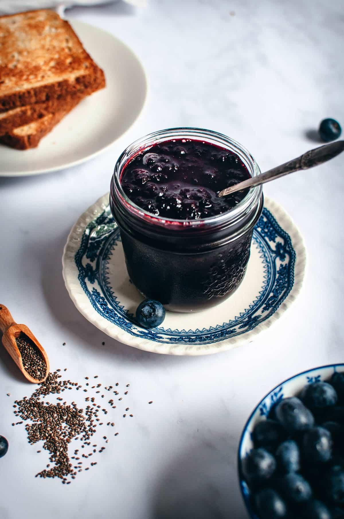 Sokeritonta mustikkahilloa avoimessa lasitölkissä, sinisen lautasen päällä.