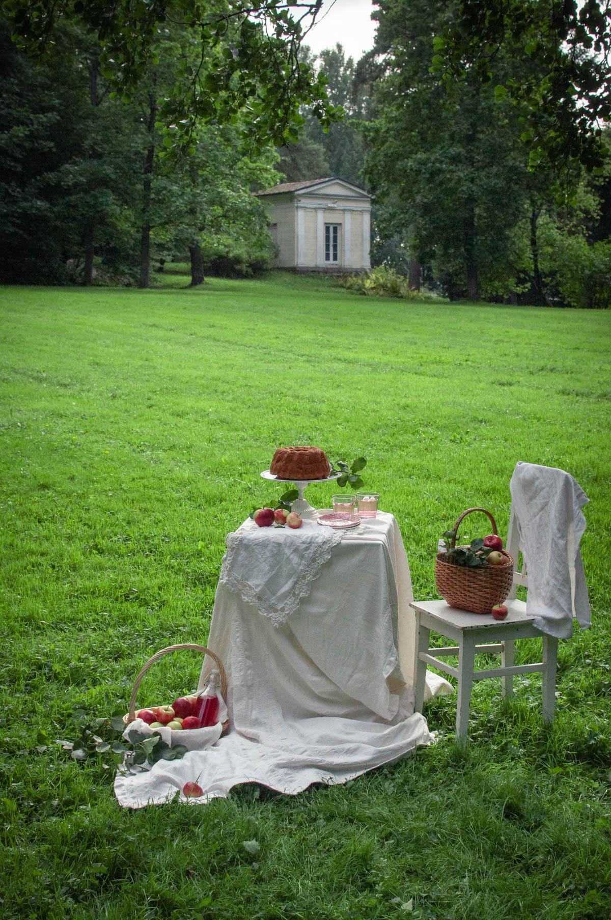 Romanttinen ulkokuva. Omekakku on katettu pienelle, valkealla liinalla peitetylle pöydälle. Taustalla näkyy Engelin suunnittelema huvimaja.