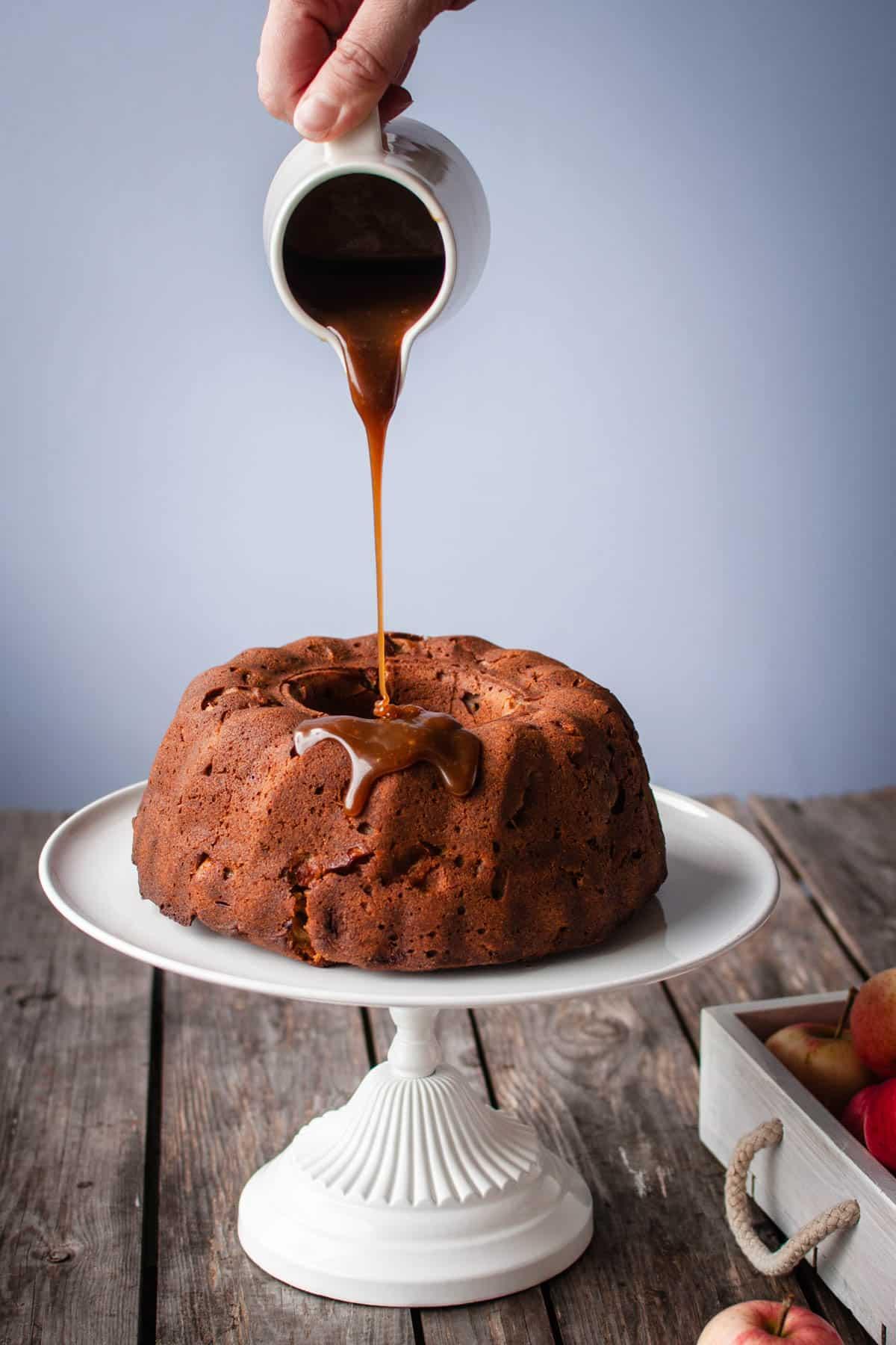 Omenakakku valkoisella kakkujalustalla puupöydällä. Kuvan ylälaidassa näkyy käsi, joka pitelee pientä valkoista kannua, josta valuu kinuskia kakun päälle.