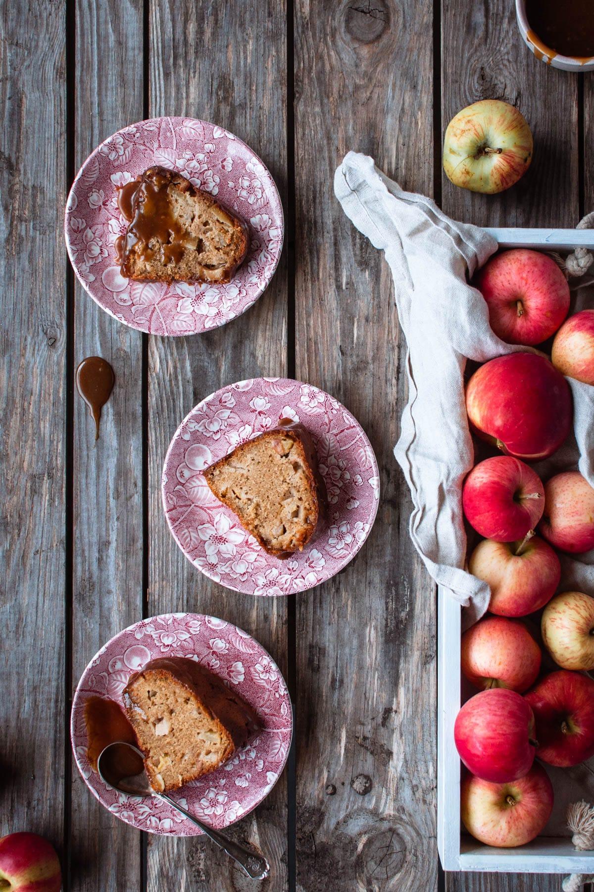 Kolme palaa omenakuivakakkua vaaleanpunaisilla lautasilla puupöydällä. Kuvan oikeassa laidassa on omenoita valkoisella puutarjottimella.