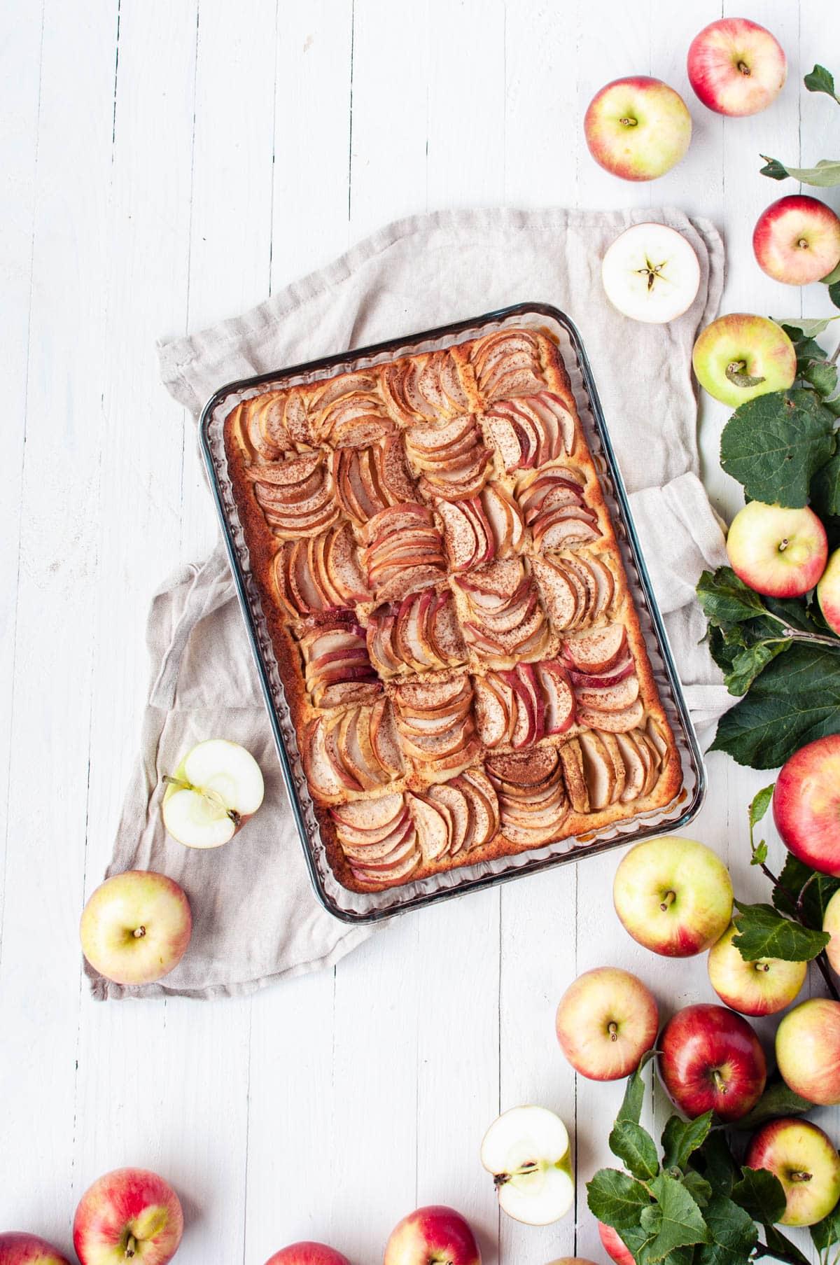 Omenapiirakka vuossaan ja tuoreita omenoita ja omenapuun lehtiä.