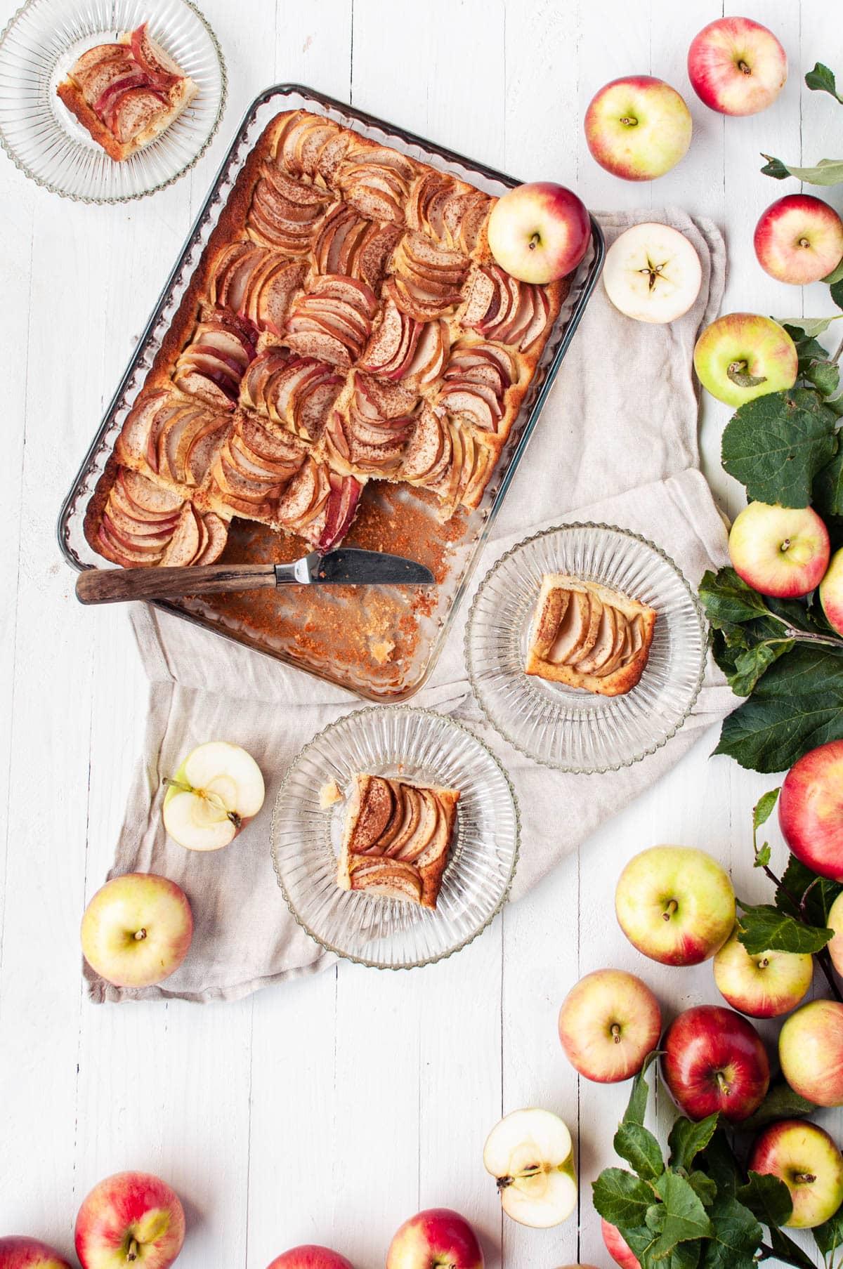 Omenapiirakka, josta on leikattu kolme palaa lautasille.