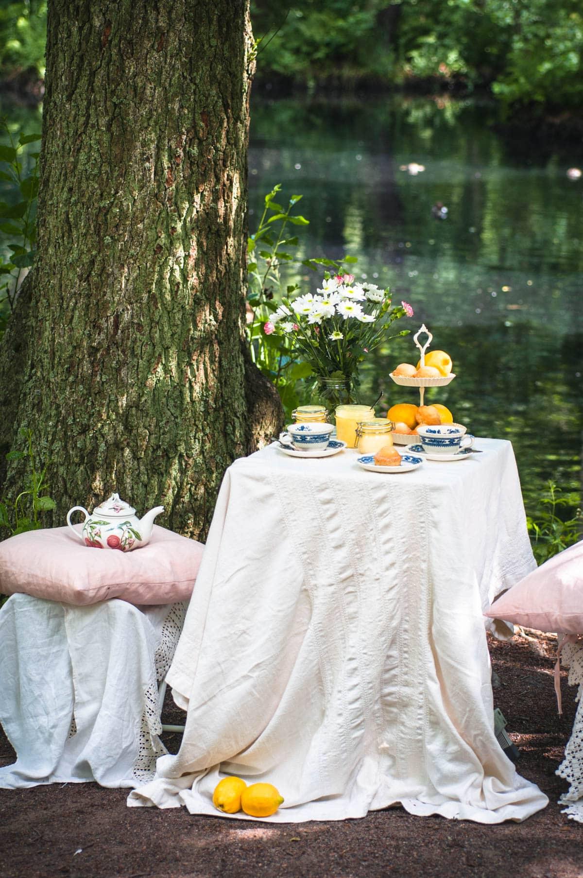 Taiteellinen valokuva pöydästä lammen rannalla. Pöydällä on valkoinen pöytäliina, jolle on katettu muffineita, teekupit ja lemon curdia.